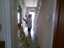 Scraping wallpaper in the foyer.