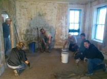 Habitat for Humanity of Berks County volunteers tearing out modern flooring and scraping wallpaper.